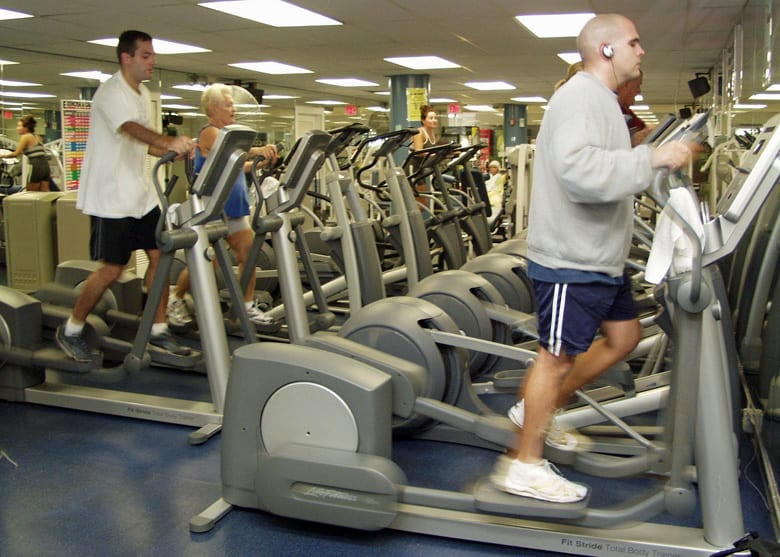 People using cross trainers at a gym