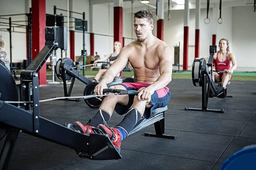 athletes resting on rowing machine